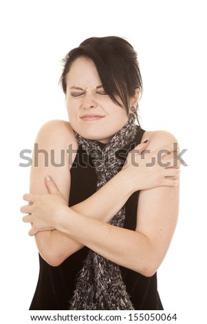 A woman with her eyes closed and arms wrapped around herself. - stock photo