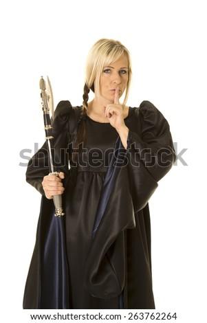 a woman with her finger up to her mouth, and a hatchet in her hand. - stock photo