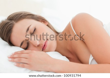 A woman with her hand in front of her  sleeping in bed. - stock photo