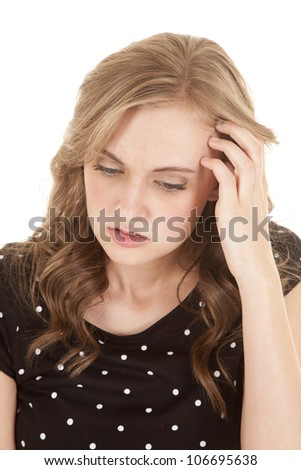 a woman with her hand in her hair with a worried expression on her face. - stock photo