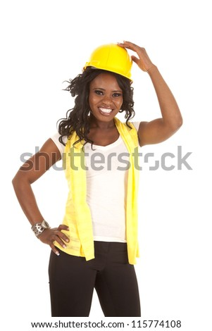 a woman with her hand on top of her hard hat with a big smile on her face. - stock photo