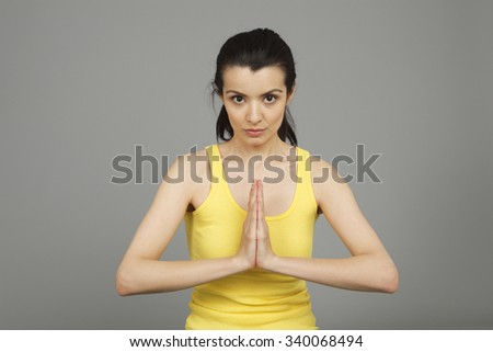 A woman with her hands together looking at viewer. - stock photo