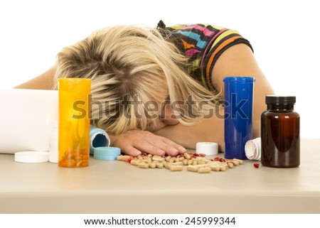 a woman with her head down on the table, with empty bottles and pills all around her. - stock photo