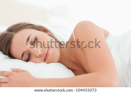 A woman with her head on the pillow sleeping in bed.