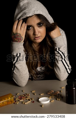 A woman with her jacket pulled over her head, looking at the pills on the table, with a troubled expression on her face. - stock photo
