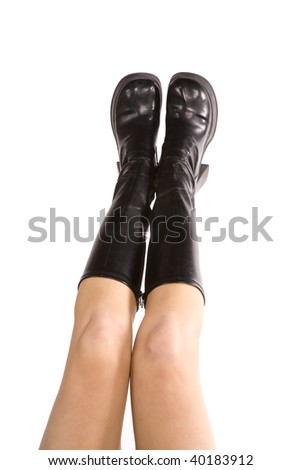A woman with her legs together with her knee high black boots.