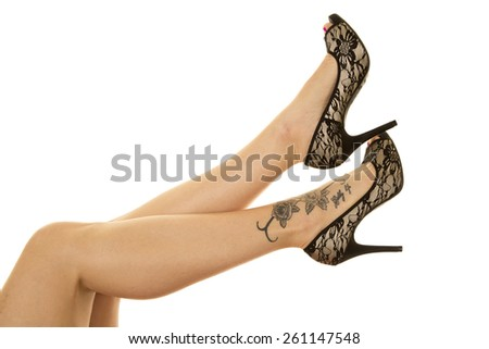 A woman with her legs up in the air, with her black lace shoes and tattoo showing. - stock photo