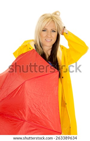 A woman with her umbrella down to the side, with a smile fixing her hair after the rain. - stock photo