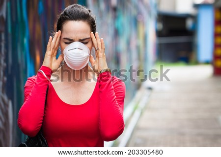 A woman with migraine or headache wearing a face mask - stock photo