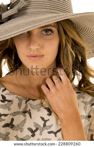 A woman with one side of her hat blocking her eye with a sensual expression.
