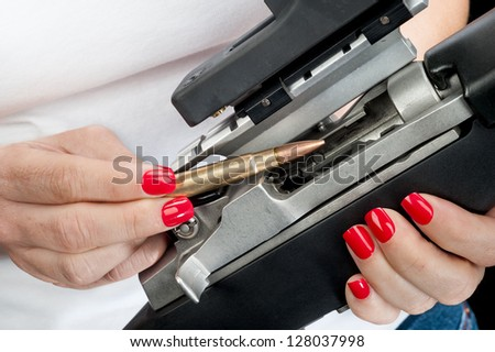 A woman with red painted fingernails loads a 223 bullet into an automatic assault rifle. - stock photo