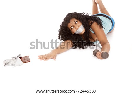 A woman with tape on her mouth is reaching for some chocolate. - stock photo