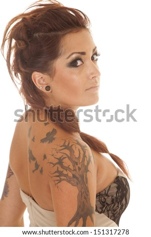 A woman with tattoos on her looking back. - stock photo