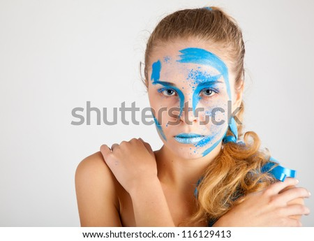 A woman with unusual make-up. Gray background