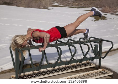 a woman working out in the outdoors doing push ups on a bike rack