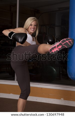 a woman working out with her kick boxing with an intense expression on her face.