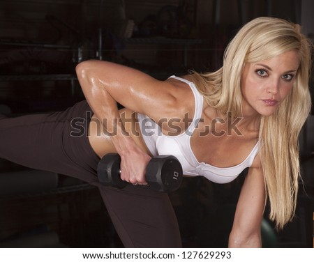 A woman working out with weights in a gym.