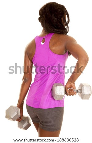 a woman working out with weights in her pink tank, and gray shorts. - stock photo