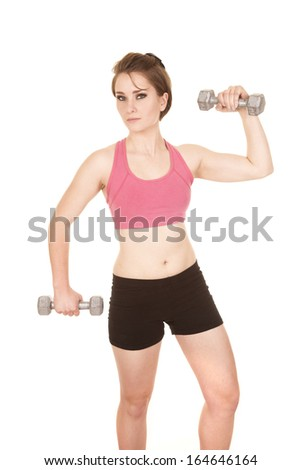 a woman working out with weights with a serious expression.