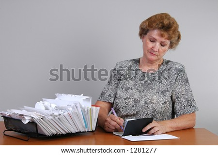 A woman writes a check to pay bills