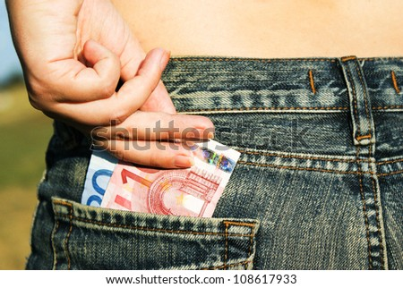 a womanish hand draws out a money from the pocket of jeans