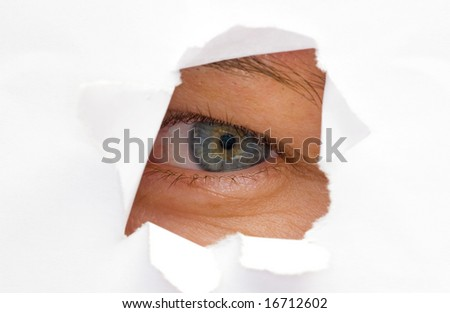 a womans eye looking trough cut paper hole