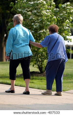 A women assist her elderly mother as they walk