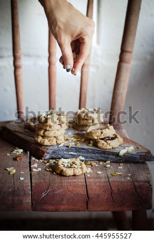 A women decorate chocolate filled cookies made of different healthy flours with seeds and nuts. Dark photo. Selective focus. Also available in horizontal format.