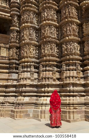 A women in a red saree looking at carvings on the walls of the Western Group of temples of Khajuraho, famous for their erotic sculptures, India. - stock photo