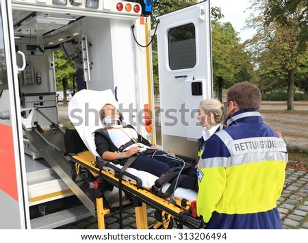 A Women on stretcher and Ambulance after accident - stock photo