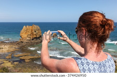 A women tourist takes a photo of Eagle Rock at Aireys Inlet on the Great Ocean Road Victoria - Australia. The coastline along the great ocean road is a spectacular road trip accessible from Melbourne - stock photo