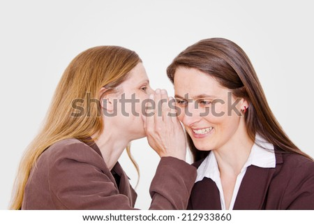 A women whispers something to the other/women/office