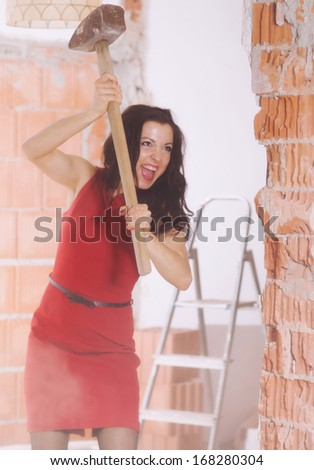 A women with a red skirt is working with a big hammer on a building site.picture is toned.