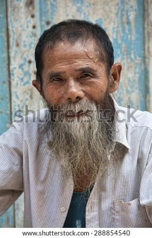 A wonderful 80 year old man with the Han Ethnic Tribe from the ancient town of Daxu, Guangxi Zhuang Autonomous Region, Guilin China - stock photo