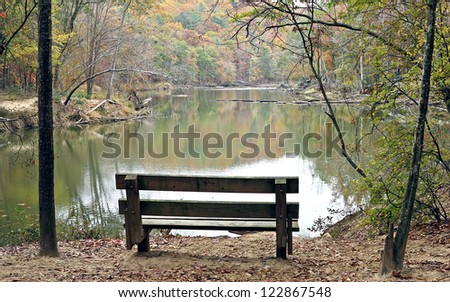 A wood bench overlooking a quiet stream in Autumn. - stock photo