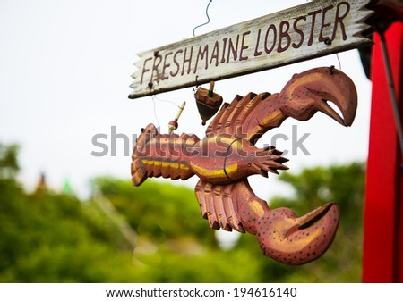 A wood hand painted and carved sign advertising fresh Maine lobster - stock photo