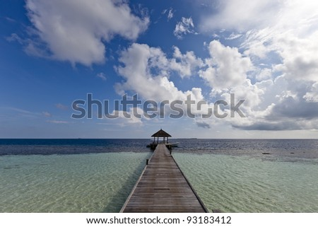 A wood pontoon go to blue lagoon and ocean front of a paradise island - stock photo