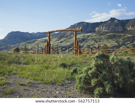 A wood ranch gate below cliffs of the Absraoka mountains in Wyoming