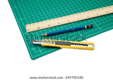 A wood ruler, cutter, cutting mat, pencil isolated over a white background - stock photo