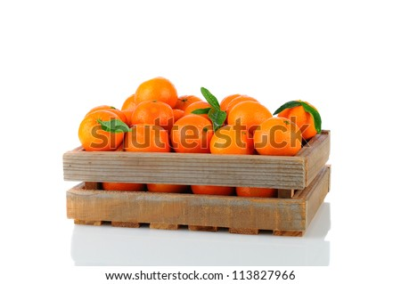 A wood rustic crate full of Clementine Mandarin Oranges. Horizontal format over a white background with reflection.