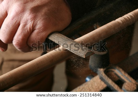 A wood worker works on a project on his lathe. Lathes are used by wood workers and metal workers for all sorts of projects around the world. Wood Working is a business and a hobby enjoyed by millions  - stock photo