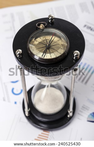A wood working(office) table(desk) with sand timer(hour glass), graph paper(document)s for business, vintage compass, top view.   - stock photo