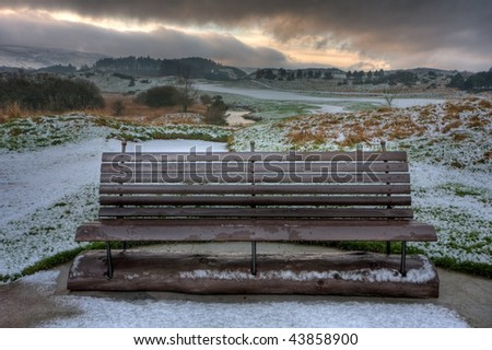 A wooden bench on an icy morning on a golf course in rural Perthshire, Scotland. HDR photo with mountains and warm morning light in the background. - stock photo