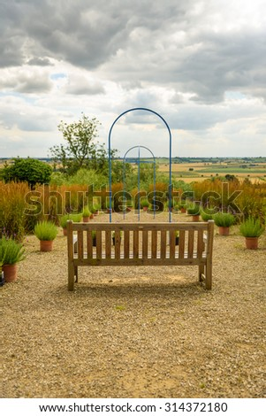 A wooden bench with views across a beautiful garden off into the distance. Suggests, retirement, career, progression path, business motivational poster etc.. - stock photo