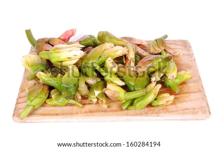 A wooden board full of freshly harvested traditional eatable South African edible waterblommetjies (Cape asparagus or Aponogeton distachyos). Image isolated on white studio background. - stock photo