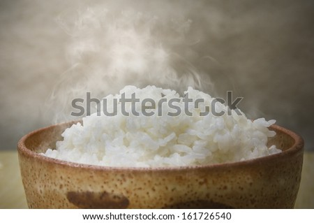 A wooden bowl filled with steaming rice. - stock photo