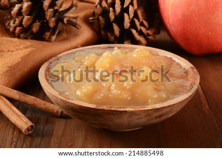 A wooden bowl of chunky applesauce with cinnamon sticks and pine cones - stock photo