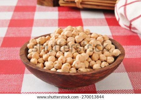 A wooden bowl of dried garbanzo beans on  a table - stock photo