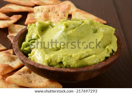 A wooden bowl of guacamole with toasted, seasoned pita chips