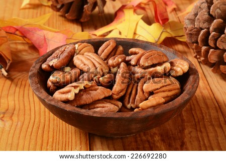 A wooden bowl of pecans on a table with pine cones and autumn leaves - stock photo